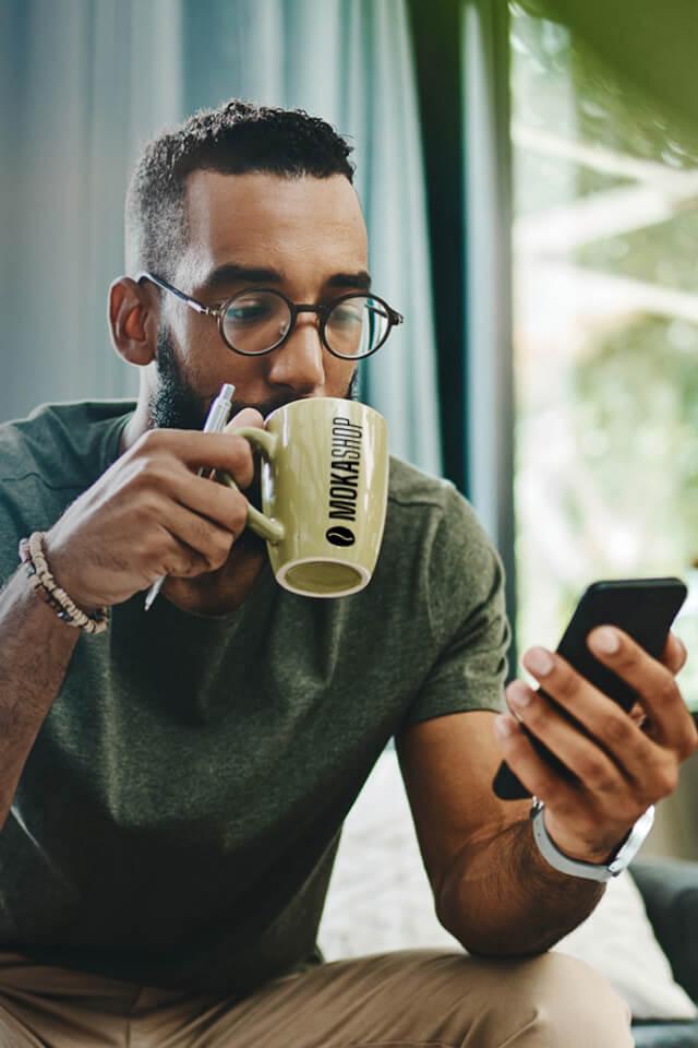 Uomo che sorseggia un caffé in una tazzina con la scritta MokaShop.
